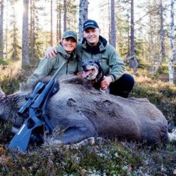 Bilde av Villmarksparet Jeanette og Jan-Robert Sveen med elghund og felt elg i skogen.