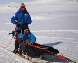 Ridderennet: Bilde av hundeslede med hundekjører og passasjer i snølige omgivelser.