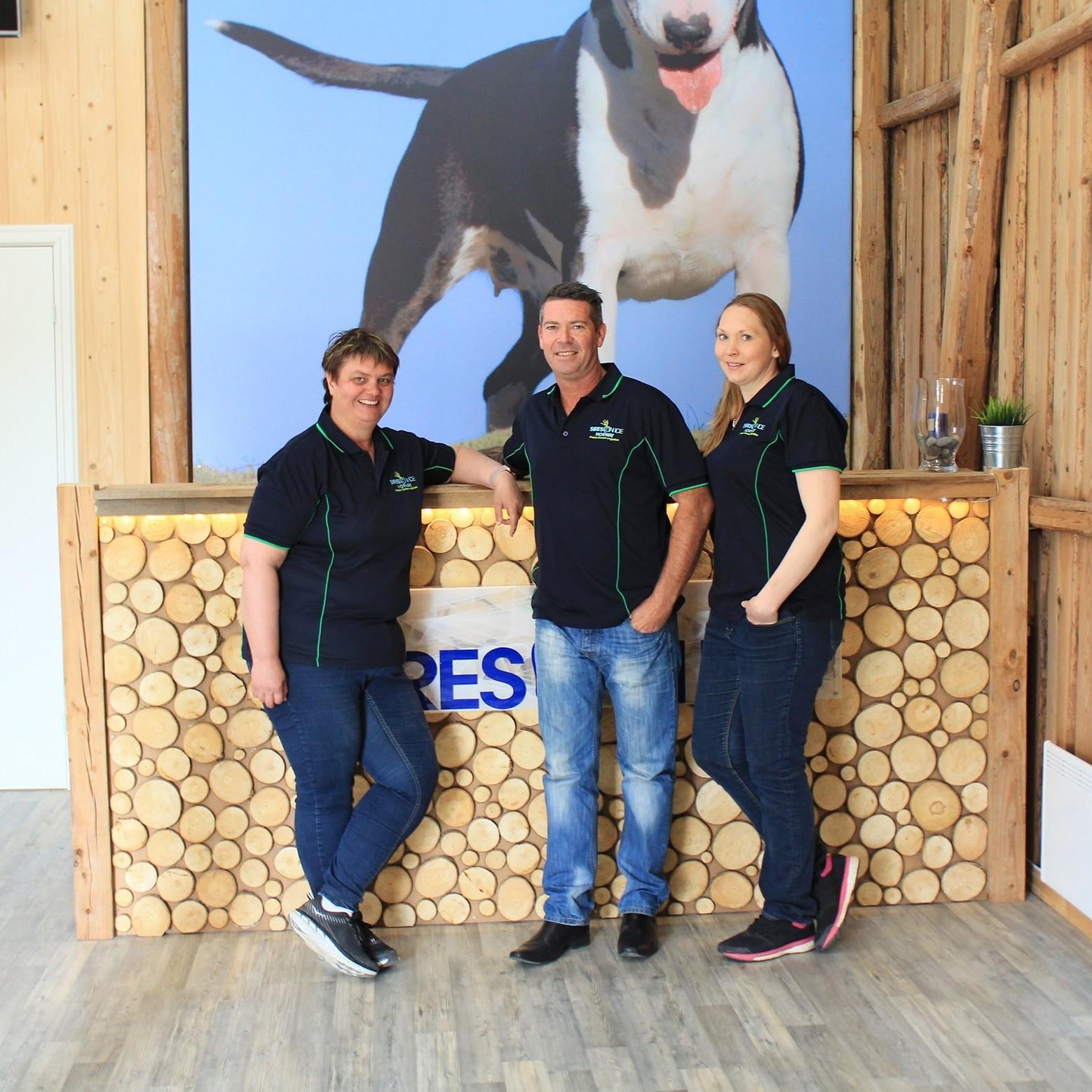Tre smilende ansatte i fullfigur